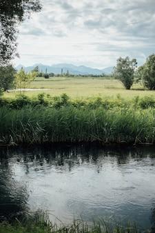 Long shot rivière traversant des terres agricoles