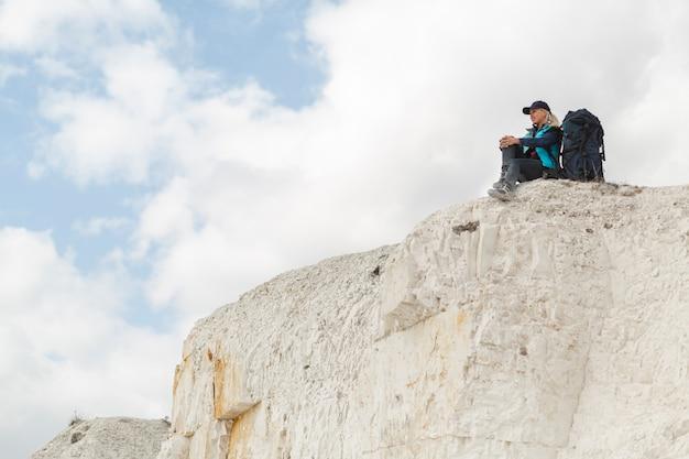 Long shot voyageur assis sur une montagne