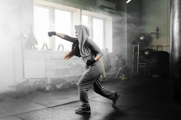 Long shot woman training in boxing center