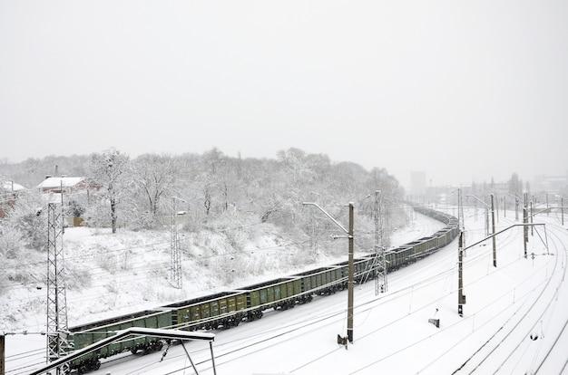 Un long train de wagons de marchandises se déplace le long de la voie ferrée. paysage ferroviaire en hiver après la neige