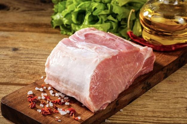 Longe de porc cru avec du sel et des herbes.