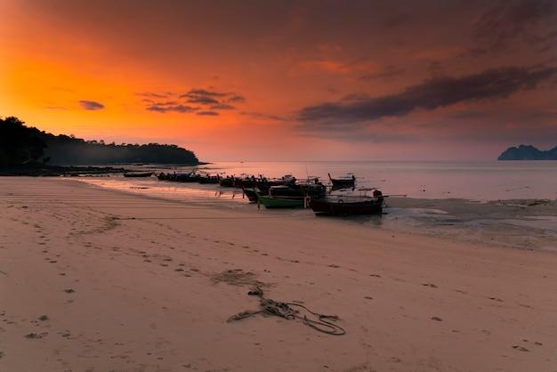 De longs bateaux se tiennent sur l'île de phi phi. coucher de soleil rose sur les îles.
