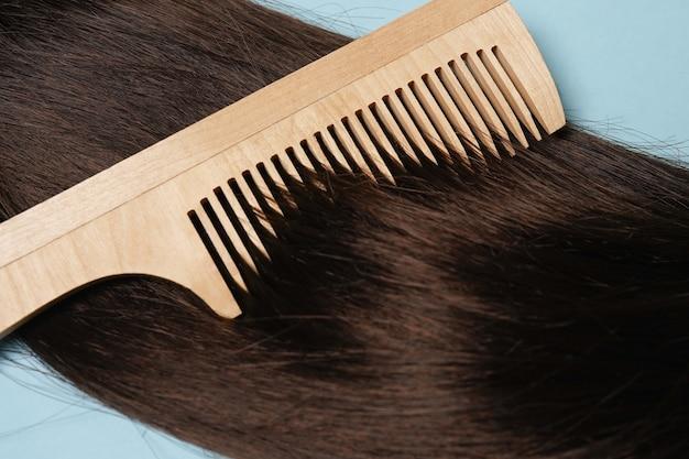 Longs cheveux bruns et brosse à cheveux en bois naturel sur fond bleu