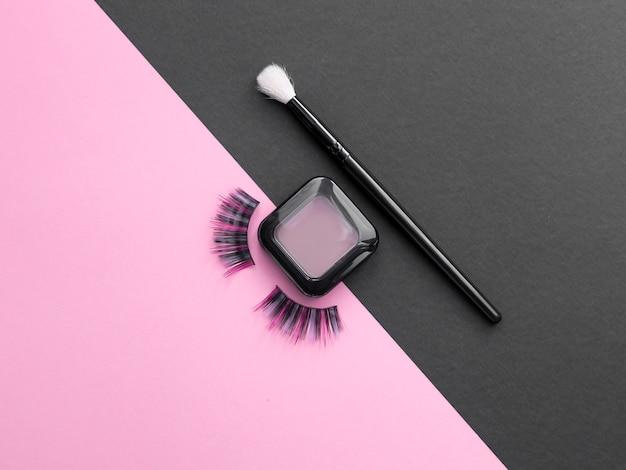 Longs cheveux colorés cils. ombre à paupières avec pinceau sur fond rose et noir.