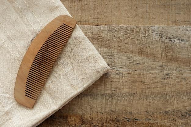 Les longs poils noirs tombent dans un peigne en bois avec un tissu blanc