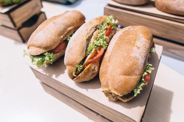 Longs sandwichs ciabatta avec laitue, tranches de tomates fraîches, concombre, jambon, salami et fromage