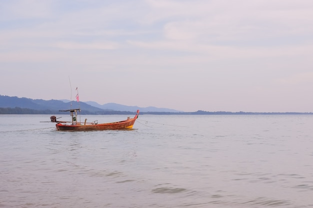 Longtail boat standing near the shore at sunset.beautiful sunset of fishing village in phang nga bay with longtail wooden fishing boat, thailand.travel by asia. paysage avec bateau de pêche traditionnel