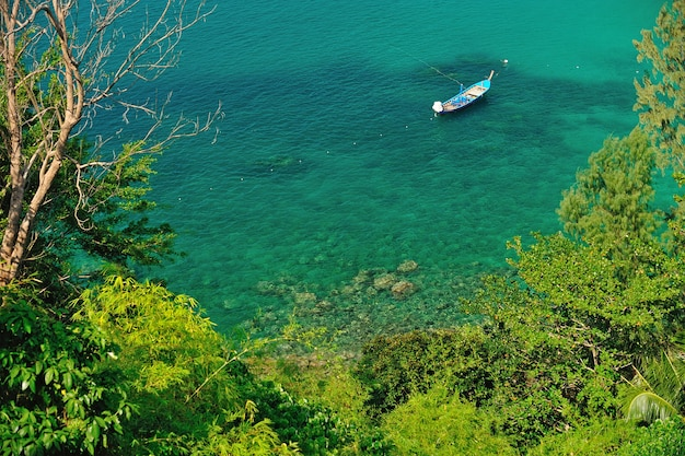 Un longtail boat traditionnel flotte dans une eau cristalline d'un bleu limpide et limpide. phuket, thaïlande