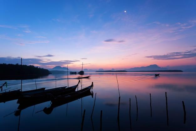 Longtail boat avec village de pêcheurs côtier, beau paysage lever de soleil sur la mer et