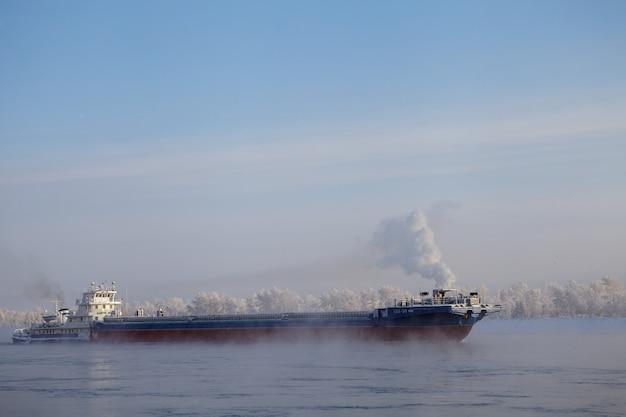 Longue barge descendant la rivière en hiver froid