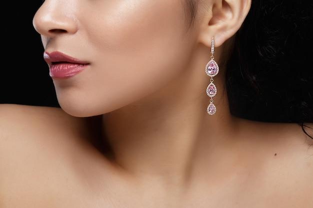 Longue boucle d'oreille avec des pierres précieuses violettes pendent de l'oreille de la femme