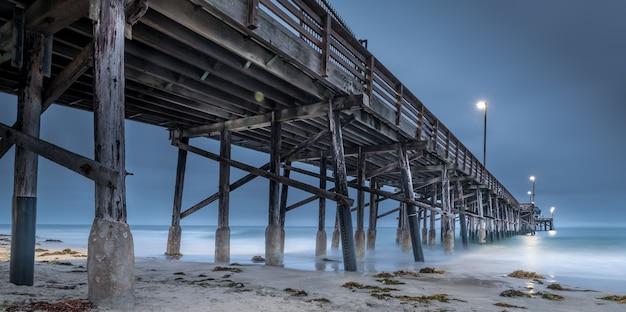 Une longue exposition d'une jetée en bois dans la mer en californie le soir