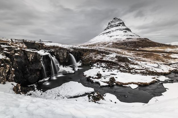 Longue exposition de montagne avec cascade au premier plan en hiver