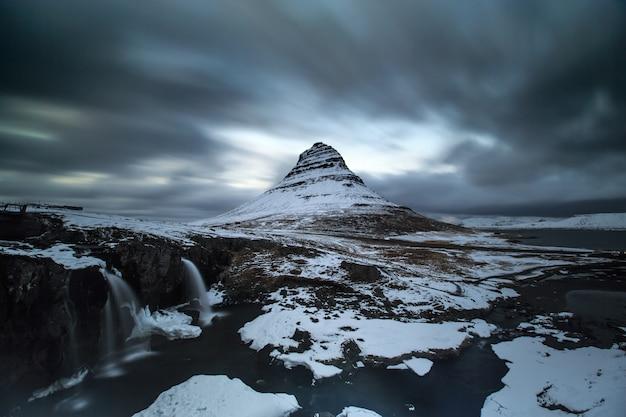Longue exposition de la montagne kirkjufell sous un nuage en mouvement