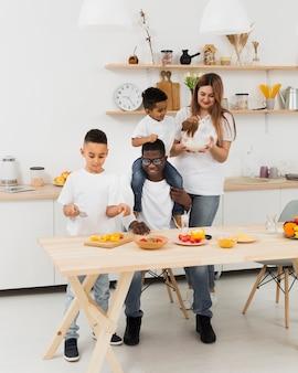 Longue famille s'amusant tout en faisant de la nourriture