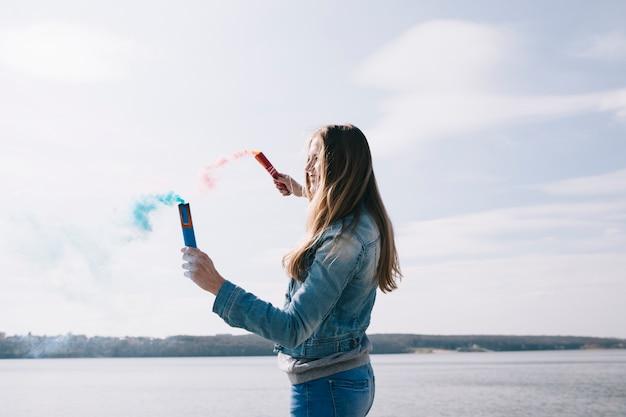 Longue femme aux cheveux tenant des torches à fumée colorées