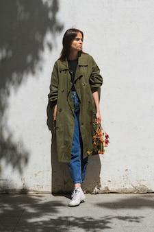 Longue femme debout tenant un bouquet de poivrons