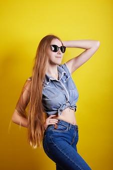 Longue fille de gingembre à lunettes de soleil pose sur fond jaune