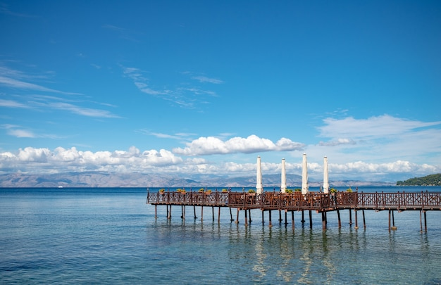 Longue jetée en bois avec un café romantique à la fin de la mer ionienne.