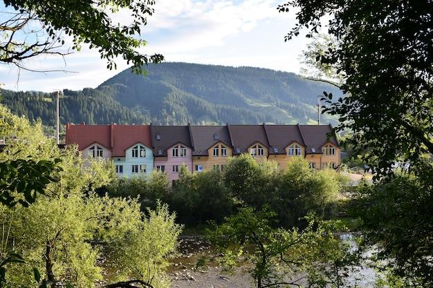 Longue maison colorée avec un toit bouclé sur fond de montagnes et d'arbres verts