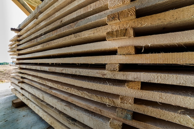 Longue pile de planches de bois soigneusement empilées à l'intérieur de la pièce du grenier en construction.