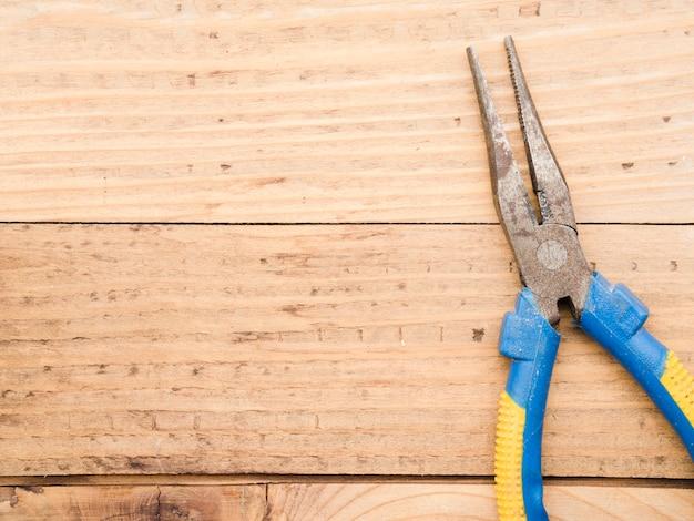 Longue pince sur table en bois