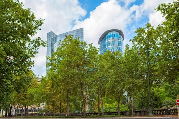 Longue rangée d'arbres le long d'un sentier dans un parc avec une clôture en fer à repasser à bruxelles, belgique
