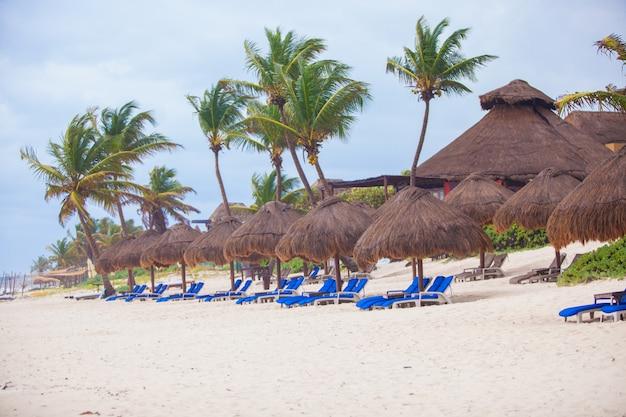 Longue rangée de chaises longues de plage bleues avec parasols sur une plage tropicale blanche