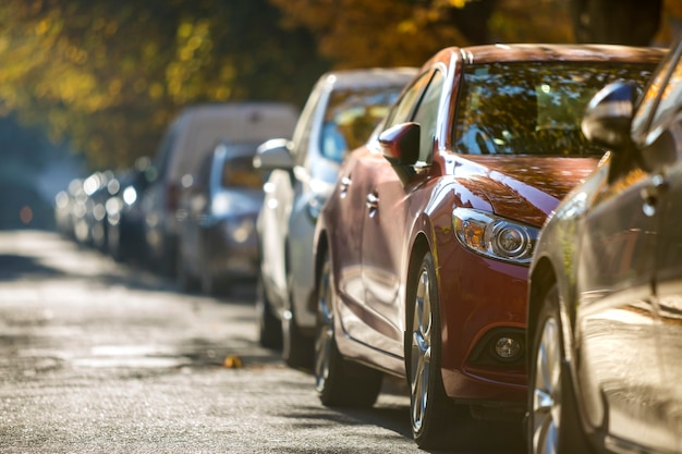 Longue rangée de différentes voitures et fourgonnettes brillantes garées le long de la route vide aux beaux jours d'automne. mode de vie de la ville moderne, concept de problème de stationnement de véhicules.