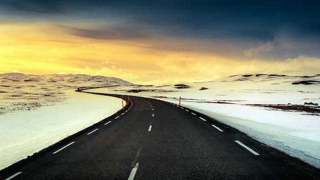 Longue route droite au coucher du soleil en hiver.