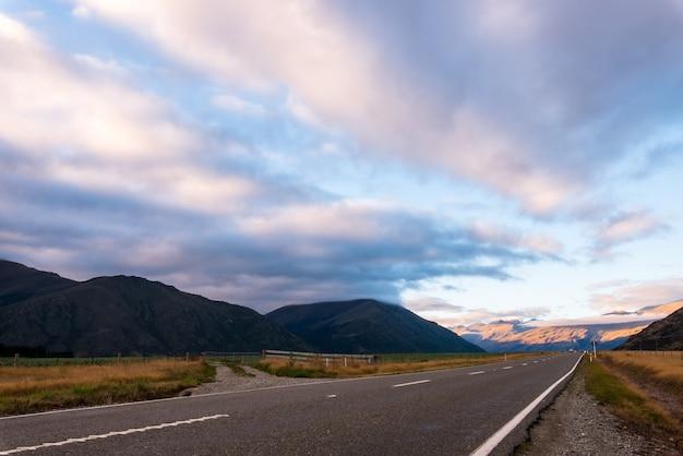Une longue route droite avec des nuages pluvieux et de la montagne en soirée