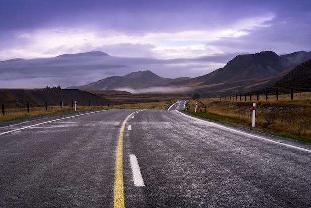Longue route locale à travers le champ d'herbe jaune et vert goto mountain qui ont des nuages derrière comme un paradis