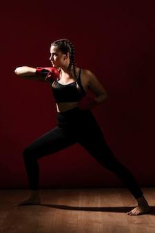 Longue vue de côté d'une femme athlétique en vêtements de fitness