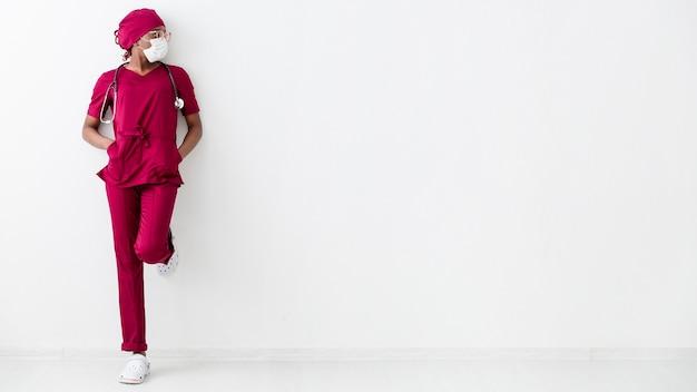 Longue vue de la femme médecin s'appuyant sur le mur blanc