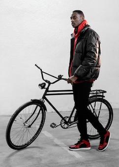 Longue vue de l'homme avec son vélo