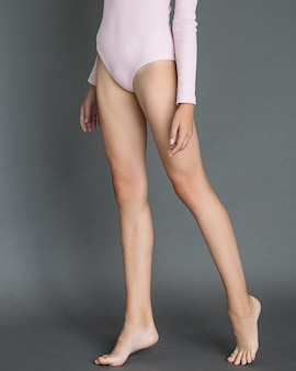 Longues jambes élancées d'une jeune fille sur fond gris sans chaussures. photo pieds nus jusqu'à la taille. body rose tendre. lumière du jour. soins de la peau du corps.