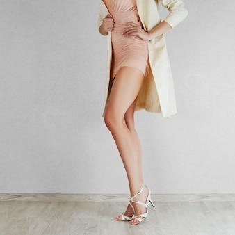Longues jambes de femme nue en sandales à talons beiges