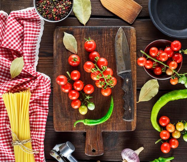 Longues spaghettis crus jaunes et tomates cerises rouges sur une table en bois marron