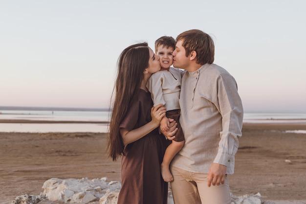 Look familial de vêtements en lin naturel sur la plage du soir. jeune famille câlins et bisous.