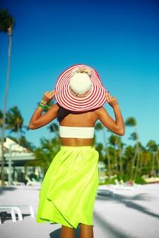 Look haute couture. dos de femme modèle glamour sexy en tissu coloré et chapeau de soleil derrière le ciel bleu de la plage