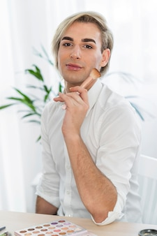 Look de maquillage masculin tenant un pinceau