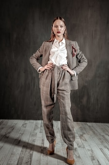 Look à la mode. jolie femme brune portant un costume chaud tout en présentant son choix
