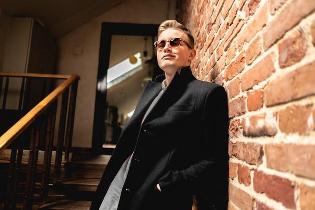 Look à la mode. mâle élégant à lunettes de soleil rester en face du mur de briques