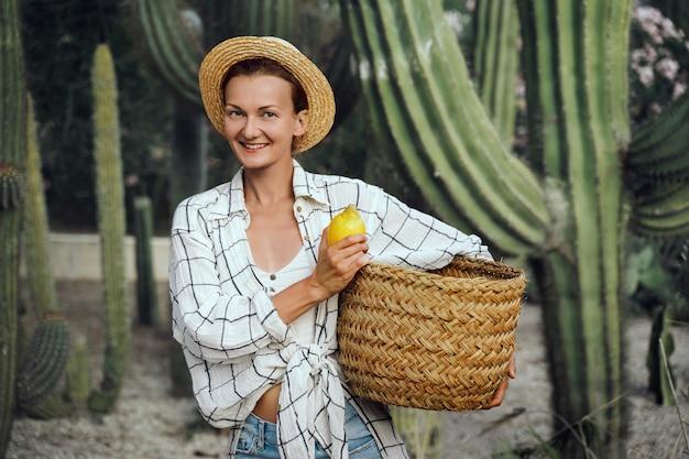 Look de mode rustique girl holding panier de citrons frais à la ferme parmi les cactus géants verts