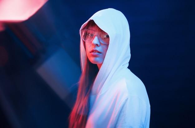 Look moderne de jeunesse. studio tourné en studio sombre avec néon. portrait de jeune fille