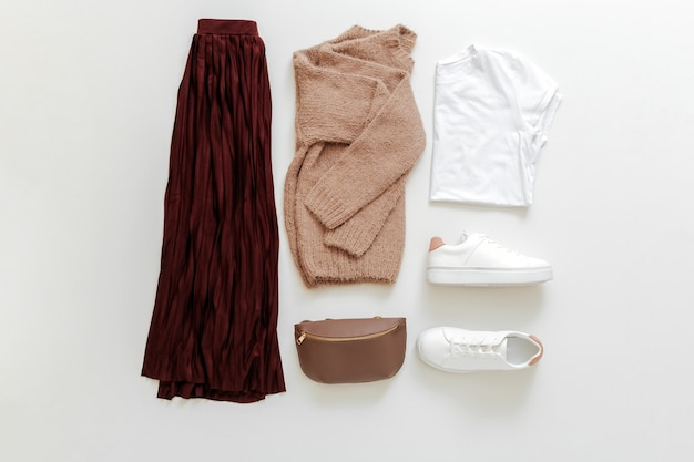 Look de printemps féminin tenue d'automne jupe bordeaux pull beige chaussures blanches baskets sac t-shirt de base blanc sur fond blanc vue de dessus à plat. vêtements pliés pour femme mode tenue basique urbaine.
