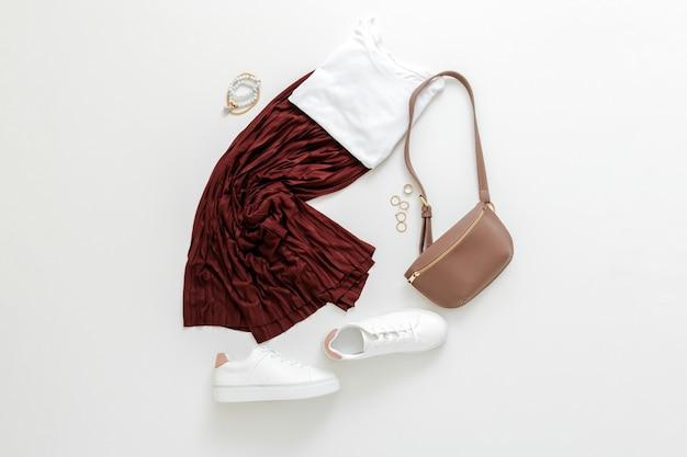 Look printemps femme tenue d'été jupe bordeaux chaussures blanches baskets sac de taille tshirt basique blanc. vêtements à mouches pliés pour femme, tenue de base urbaine avec accessoires. vue de dessus.