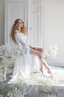 Look romantique blonde bouclée, beaux yeux. fleurs sauvages blanches dans les mains. fille robe légère blanche et cheveux bouclés, portrait de femme avec des fleurs à la maison près de la fenêtre, pureté et innocence