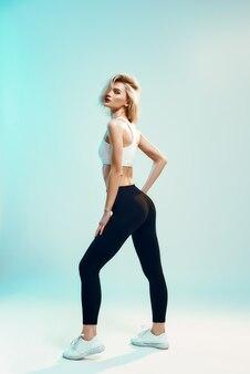 Look sportif jeune femme en haut blanc et leggings noirs avec un corps parfait regarde