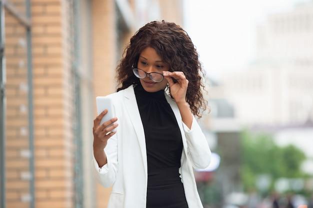 Lookint de femme d'affaires au téléphone